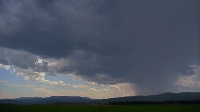 wide shot time lapse storm clouds rolling over valley / mountains in background - western usa stock videos & royalty-free footage