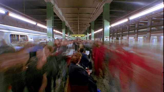 Wide shot time lapse subway passengers entering and exiting trains on platform / New York City