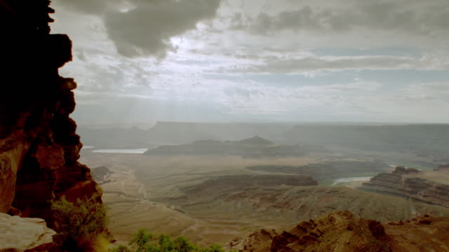 wide shot pan time lapse sun rays + clouds over weathered canyon / canyonlands national park, utah - キャニオンランズ国立公園点の映像素材/bロール