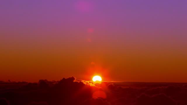 vídeos de stock, filmes e b-roll de wide shot time lapse sun rising above clouds - horizonte