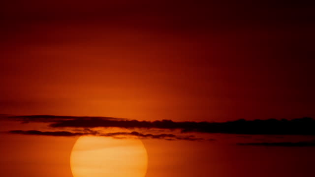 wide shot time lapse sun rising behind clouds in orange sky - sunrise dawn stock videos & royalty-free footage