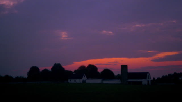 Wide shot time lapse sun rising over farm with animals grazing in foreground / Richmond, Virginia