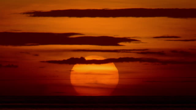Wide shot time lapse sun rising over ocean and behind clouds in orange sky