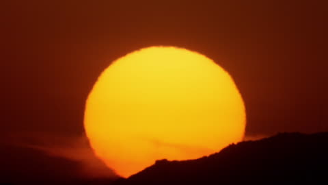 wide shot time lapse sun setting behind hillside in red sky with heat waves - the end stock videos & royalty-free footage