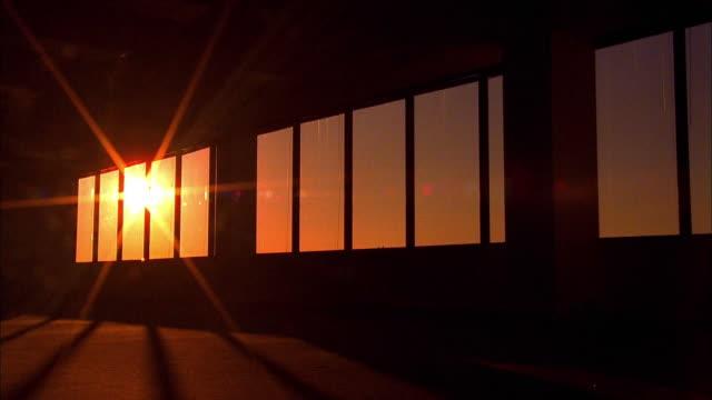 wide shot time lapse sun setting in orange sky through windows of dark empty office - day stock-videos und b-roll-filmmaterial