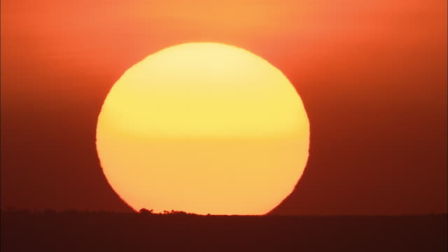 wide shot time lapse sun setting on horizon / kenya, africa - sky only stock videos and b-roll footage