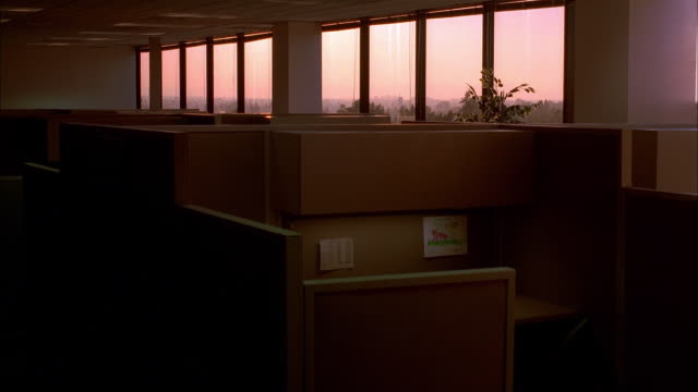 wide shot time lapse sun setting through windows of dark empty office - desk stock videos & royalty-free footage