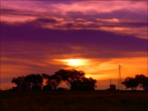 wide shot time lapse sunrise over silhouetted Texas ranch or farm + trees