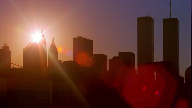 wide shot time lapse sunset behind silhouetted buildings in downtown manhattan with water in foreground / new york city - world trade centre manhattan stock videos and b-roll footage
