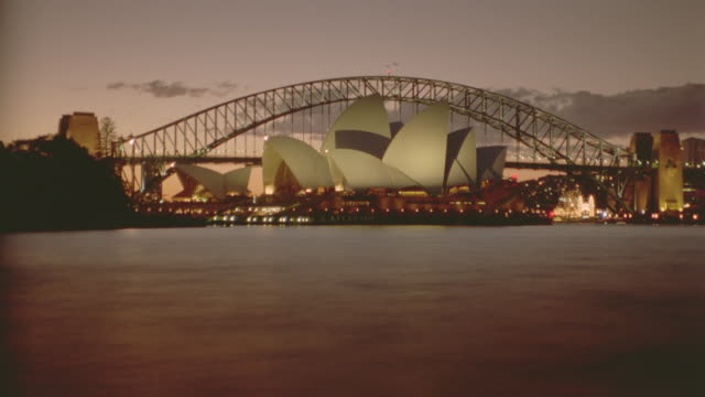 wide shot time lapse sunset behind Sydney Opera House + harbor bridge / Sydney, Australia