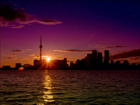 wide shot time lapse sunset over Toronto skyline / Lake Ontario in foreground