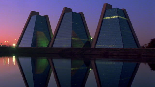 wide shot time lapse three pyramidal office buildings reflected in water in foreground at dusk / indianapolis, indiana - indiana stock videos & royalty-free footage
