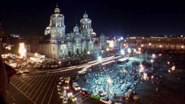 Wide shot time lapse traffic and pedestrians in Zocalo or town square w/cathedral at night / Mexico City