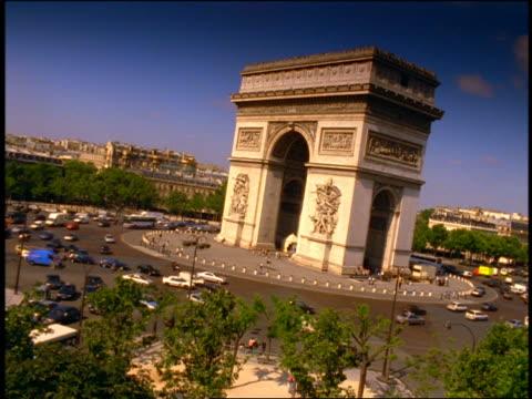 vidéos et rushes de canted wide shot time lapse traffic driving around arc de triomphe / paris, france - arc élément architectural