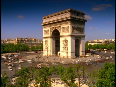 vidéos et rushes de wide shot time lapse traffic driving around arc de triomphe / paris, france - arc élément architectural