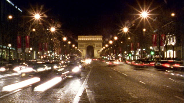 wide shot time lapse traffic in front of arc de triomphe at night / paris - monument stock videos & royalty-free footage
