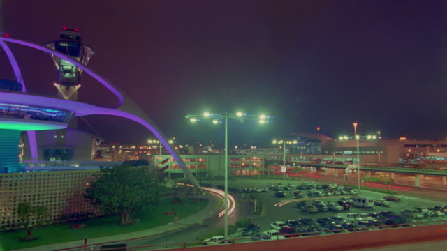 stockvideo's en b-roll-footage met wide shot pan time lapse traffic in front of lax terminal + theme building with changing lights at night - lax airport