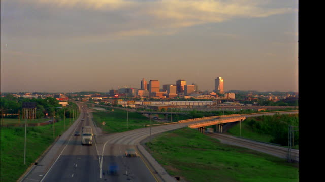 wide shot time lapse traffic moving along highways with office buildings in background / Nashville, TN