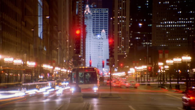 Wide shot time lapse traffic moving on downtown street at night / Chicago