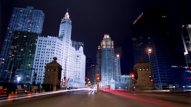 vídeos y material grabado en eventos de stock de wide shot time lapse traffic moving on downtown street at night / chicago - edificio wrigley