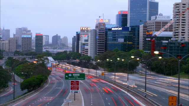 Wide shot time lapse traffic on Bradfield Highway w/downtown skyscrapers / Sydney