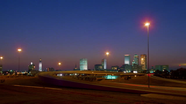 wide shot time lapse traffic on highway ramp with tulsa skyline in background / dusk to night / oklahoma - oklahoma stock videos & royalty-free footage