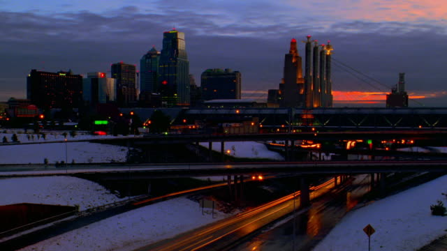 wide shot time lapse traffic on highway with overpasses at night in winter / kansas city skyline in background / missouri - 1996 stock videos & royalty-free footage
