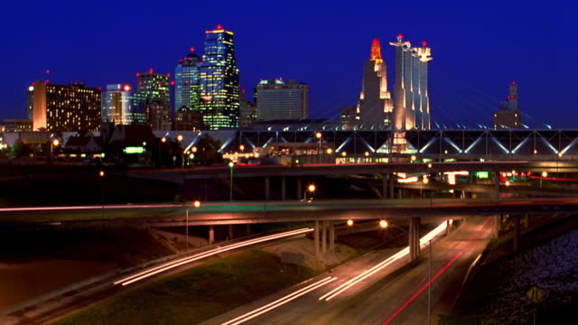 wide shot time lapse traffic on highway with overpasses at night in winter / kansas city skyline in background / missouri - kansas city kansas stock videos & royalty-free footage