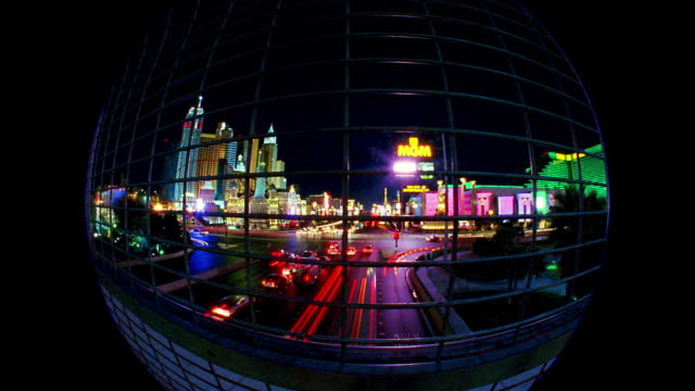 wide shot time lapse traffic on las vegas strip through fencing on highway overpass at night / las vegas, nevada - fish eye lens stock videos & royalty-free footage