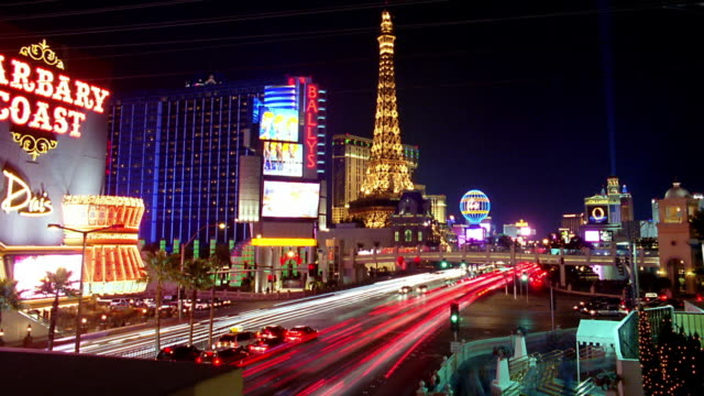 wide shot time lapse traffic on las vegas strip with eiffel tower at paris las vegas hotel and casino at night - replica della torre eiffel video stock e b–roll