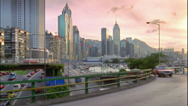 wide shot time lapse traffic on overpass above highway / skyline in background / hong kong - 1996 stock videos and b-roll footage