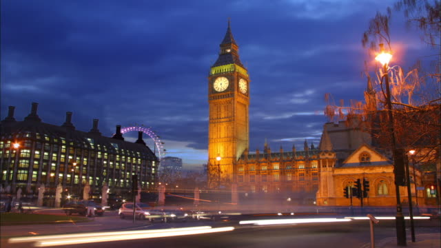 Wide shot time lapse traffic passing Big Ben and Houses of Parliament / London