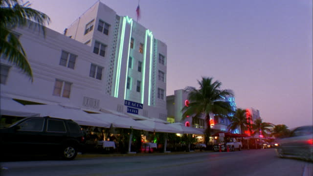Wide shot time lapse traffic passing building day to night / Miami Beach, Florida