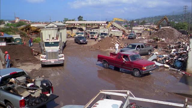 wide shot time lapse trucks arriving at and leaving garbage dump - ゴミ収集車点の映像素材/bロール