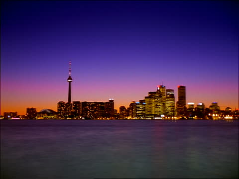 wide shot time lapse twilight to night skyline of toronto / lake ontario in foreground - toronto stock videos & royalty-free footage