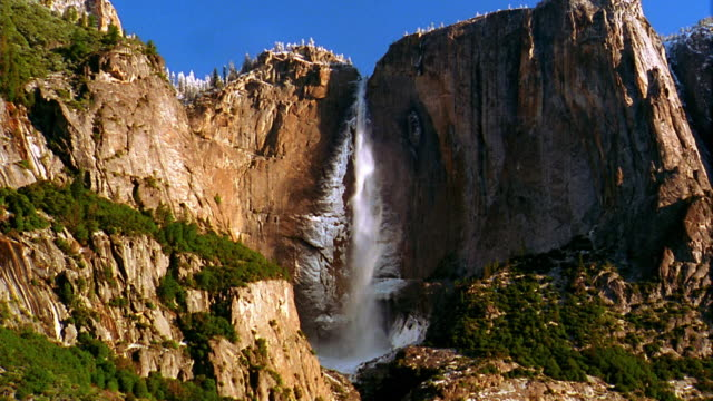 wide shot time lapse upper yosemite falls over cliff with mist / yosemite national park, california - upper yosemite falls stock videos & royalty-free footage
