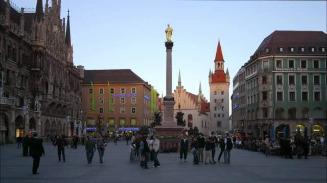 Wide shot time lapse view of people walking around Marienplatz with Toy Museum in background day to night / Munich, Germany