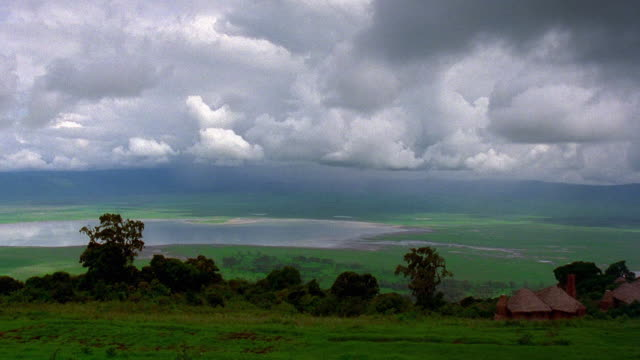 Wide shot time lapse white clouds and storm clouds moving over valley with straw huts + lake / Tanzania