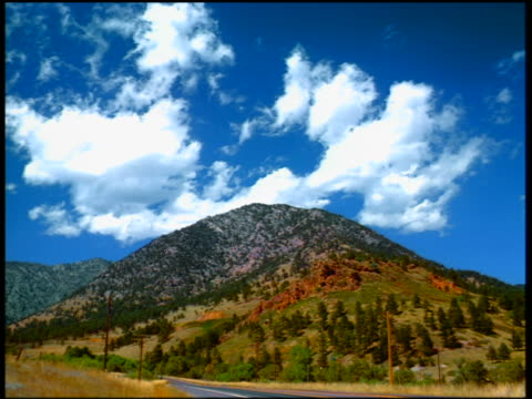 wide shot time lapse white fluffy clouds in blue sky over tree-covered mountain / boulder, colorado - 巨礫点の映像素材/bロール