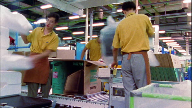wide shot time lapse workers packing television sets in boxes on assembly line / seoul, south korea - electrical equipment video stock e b–roll