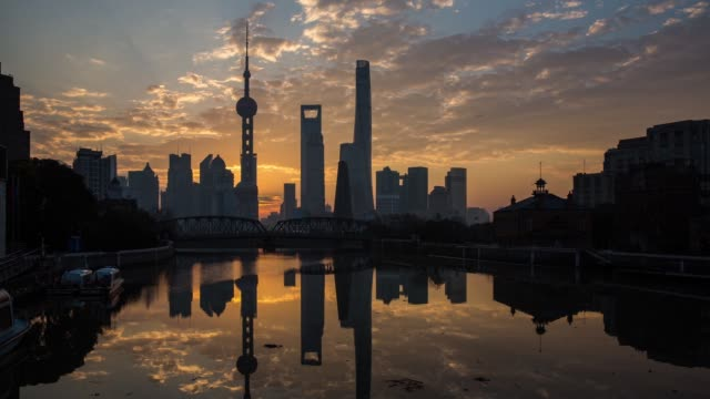 Wide shot timelapse of sunrise over Waibaidu Bridge and Huangpu River silhouetting the Oriental Pearl Tower and other buildings in the financial...