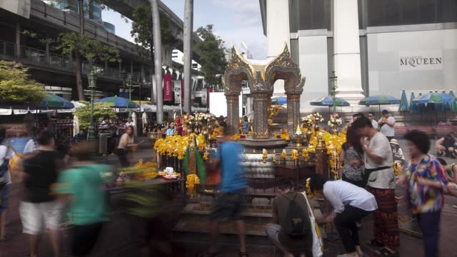 wide shot, timelapse pan left to right, of worshippers praying with incense sticks at erawan shrine in the pathum wan district of bangkok, thailand,... - エラワン聖堂点の映像素材/bロール