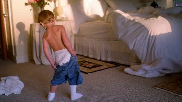 wide shot toddler boy in diapers putting on pair of denim shorts in bedroom - nappy stock videos & royalty-free footage