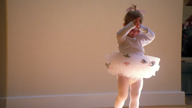 Wide shot toddler in ballerina outfit turning in place and smiling