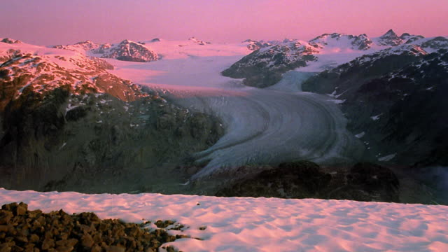 Wide shot top of glacier with time lapse shadows and light of sunrise / Coast Mountains, Whistler, British Columbia