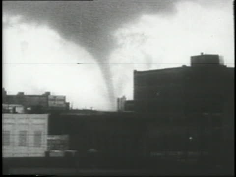 b/w 1957 wide shot tornado spinning behind buildings / texas - 1957 stock videos & royalty-free footage