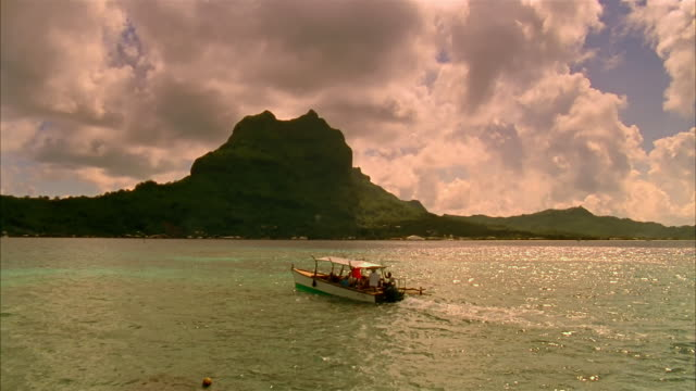 wide shot tour boat passing by mount otemanu at sunset / - bora bora stock videos and b-roll footage