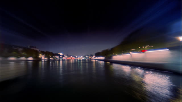 wide shot tour boat point of view under illuminated bridges on river seine at night / paris, france - boat point of view stock videos & royalty-free footage