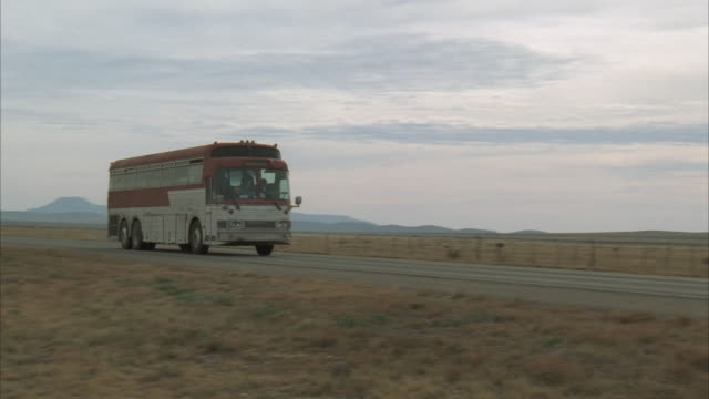 Wide Shot, PAN, Tour bus driving on highway in rural area, USA