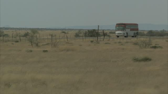 stockvideo's en b-roll-footage met wide shot, pan, tour bus driving on highway in rural area, usa - dubbeldekker bus